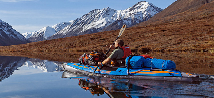 Man in a loaded touring kayak