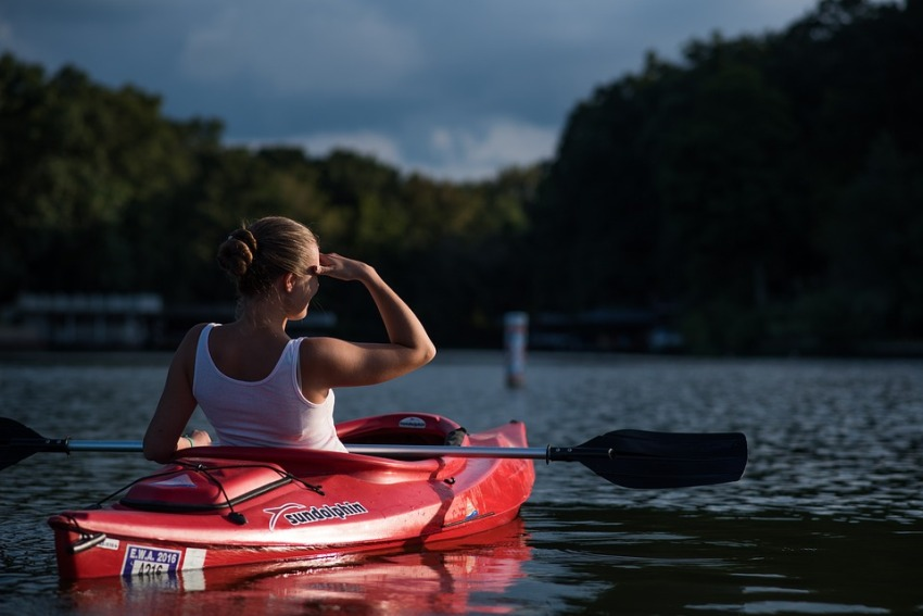 A girl in a red kayak looks into the distance