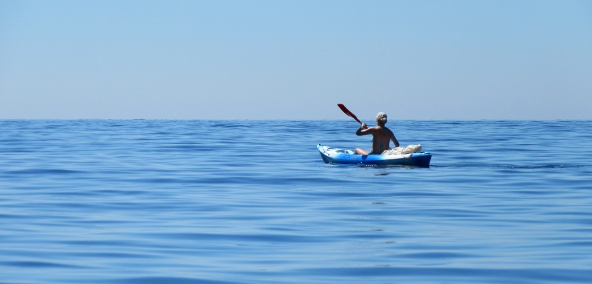 A man in a boat in the mid-ocean