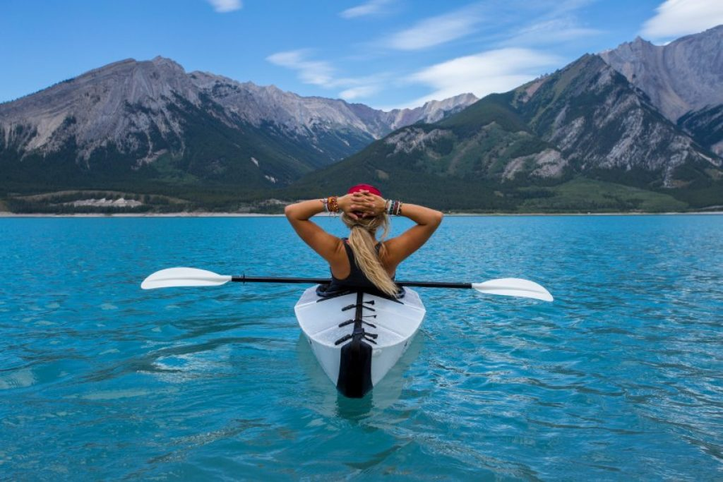 A girl in a white kayak in the blue water observes picturesque mountain scenery