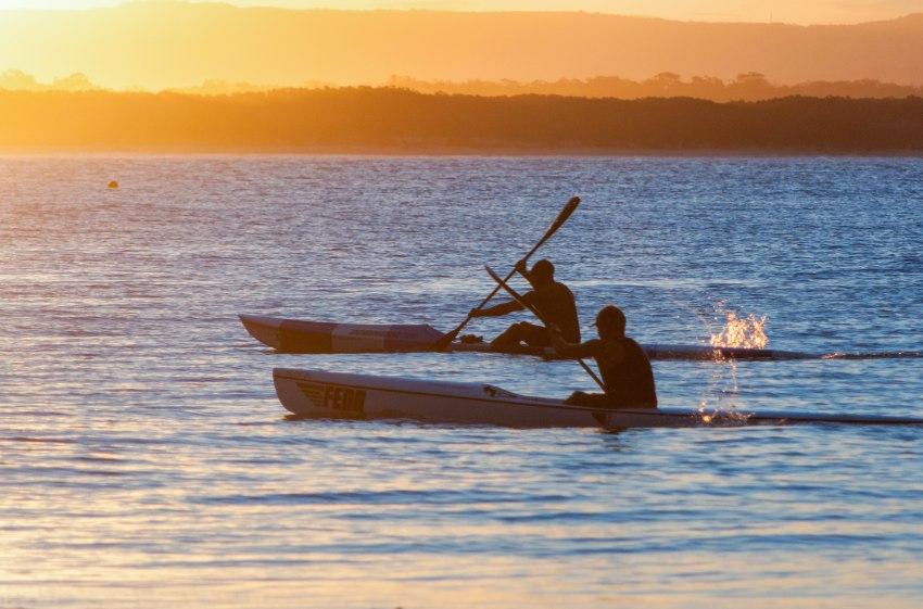 Two men paddling kayaks outlined against the sunset