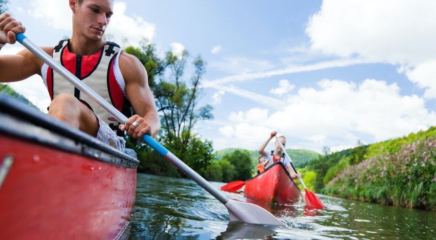 A muscled man paddling a red kayak followed by a lady and a child in another red kayak