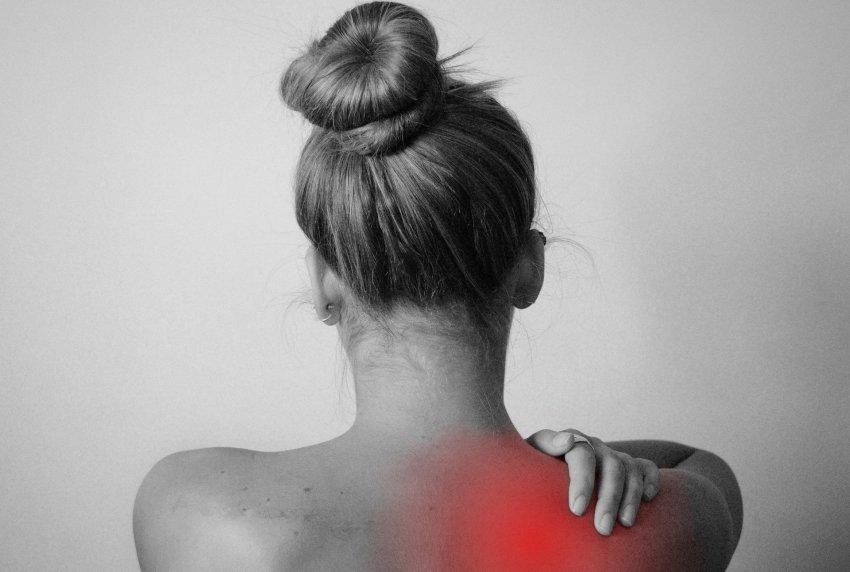 A woman rubbing her sore shoulder