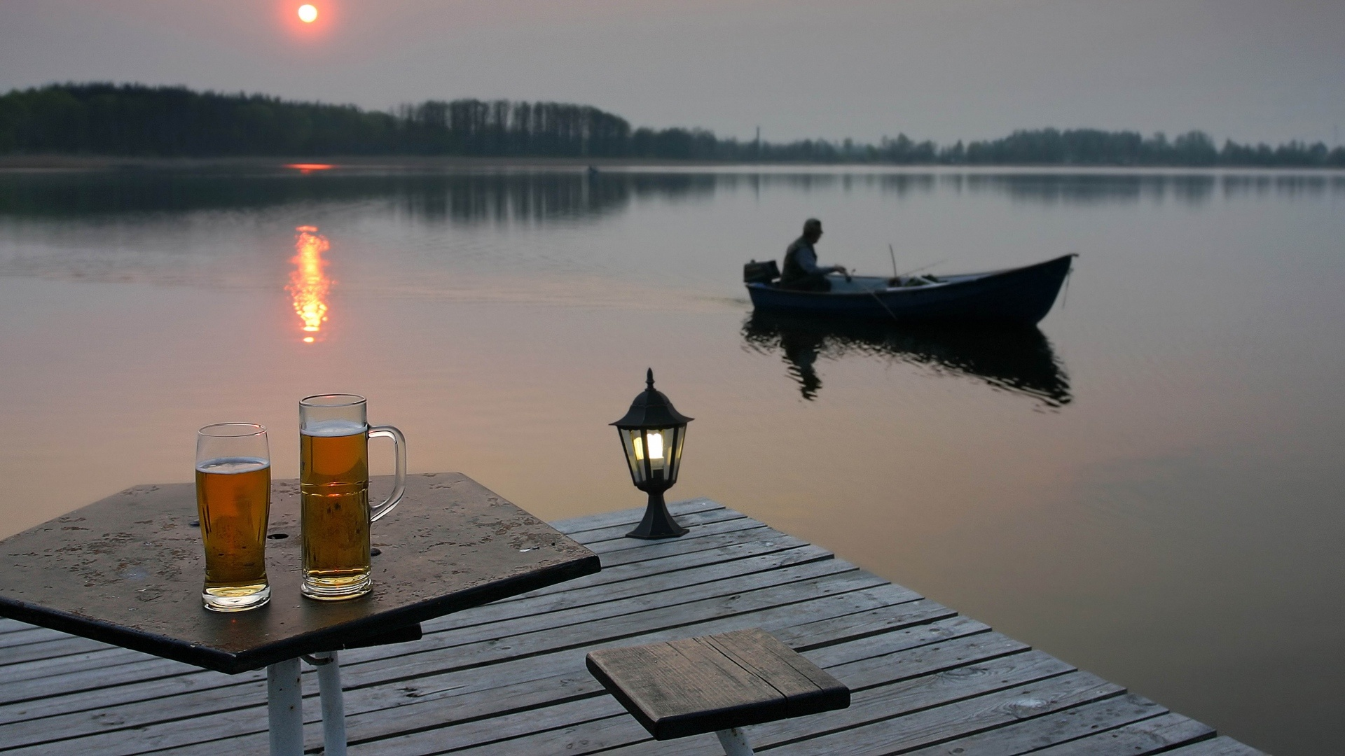 Two beer glasses on the table and a man in a boat against the sunset