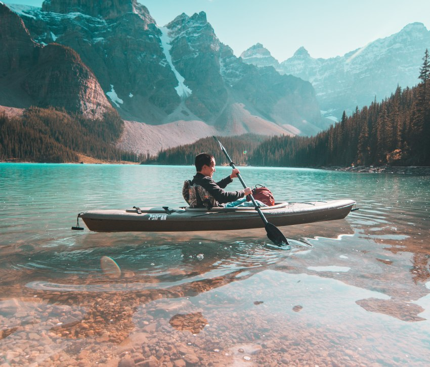 A happy man in a kayak paddling in crystal clear waters against the dense woods and snowy mountain slopes