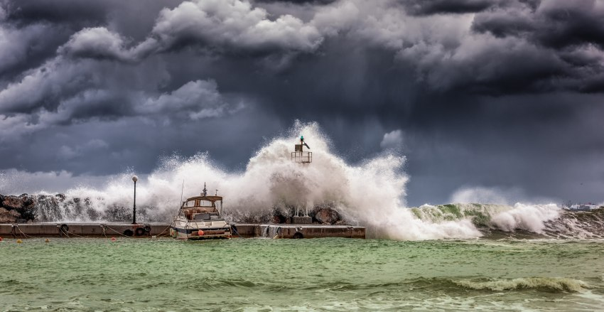 Grey sky and stormy high waves at the pier with a lonely vessel