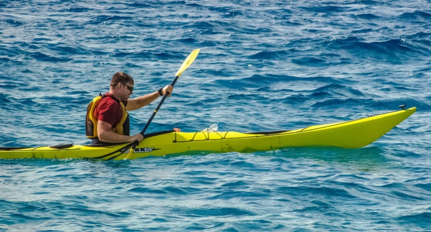 A man in a yellow kayak fighting with tidal currents