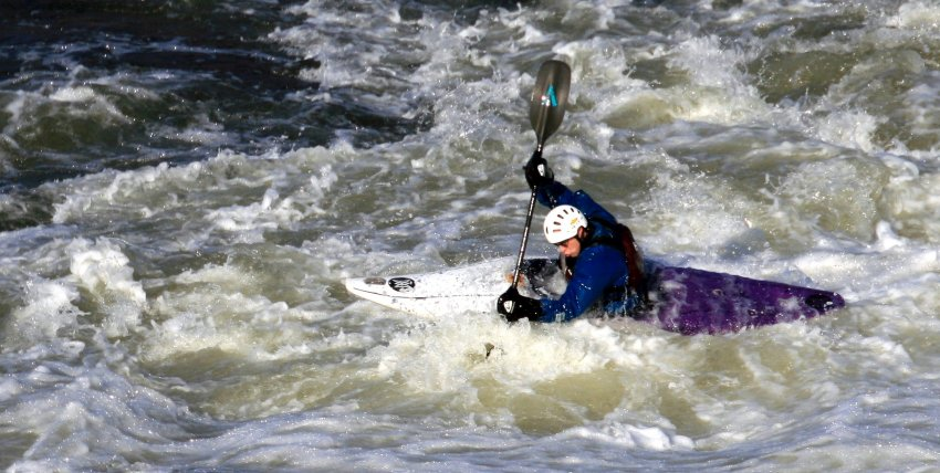 A man paddling a white-purple kayak in the whitewater