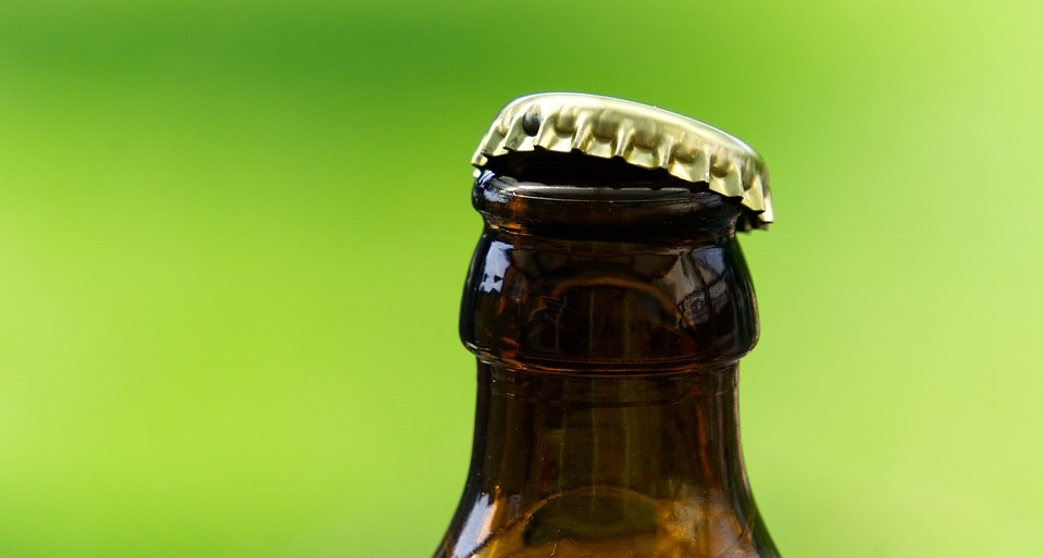 A beer bottle neck with an half-open cap