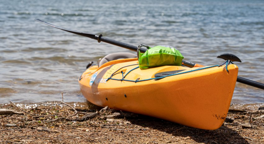 A yellow kayak resting on the shore